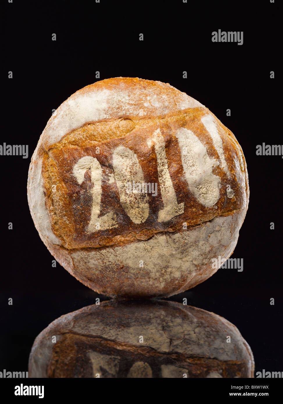 round loaf of bread dusted with the year date - Stock Image