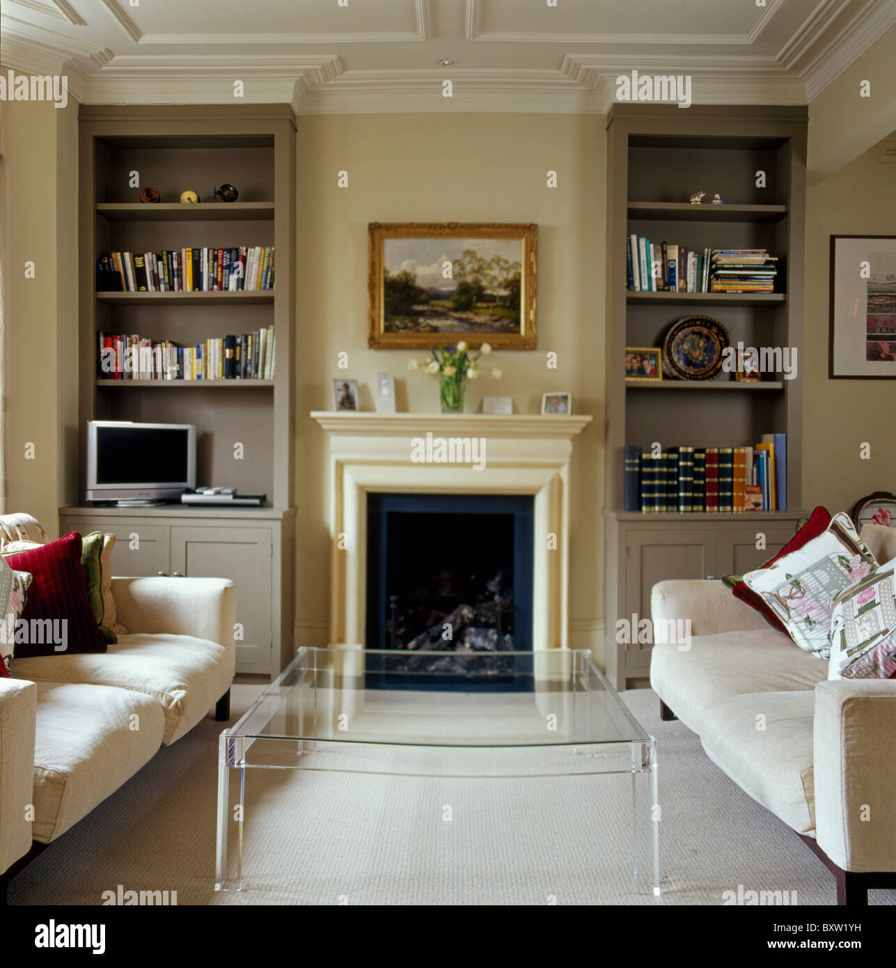 Modern Perspex Table And Cream Sofas In Traditional Cream Living Room With  Alcove Shelves On Either Side Of Fireplace