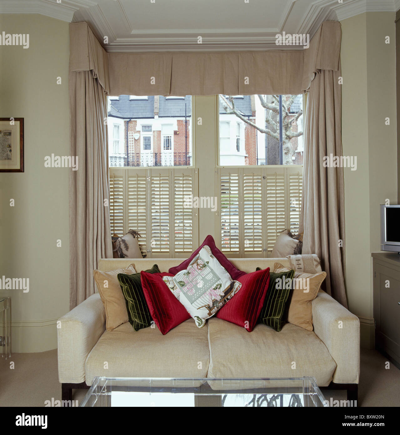 Cream sofa piled with cushions in front of window with ...