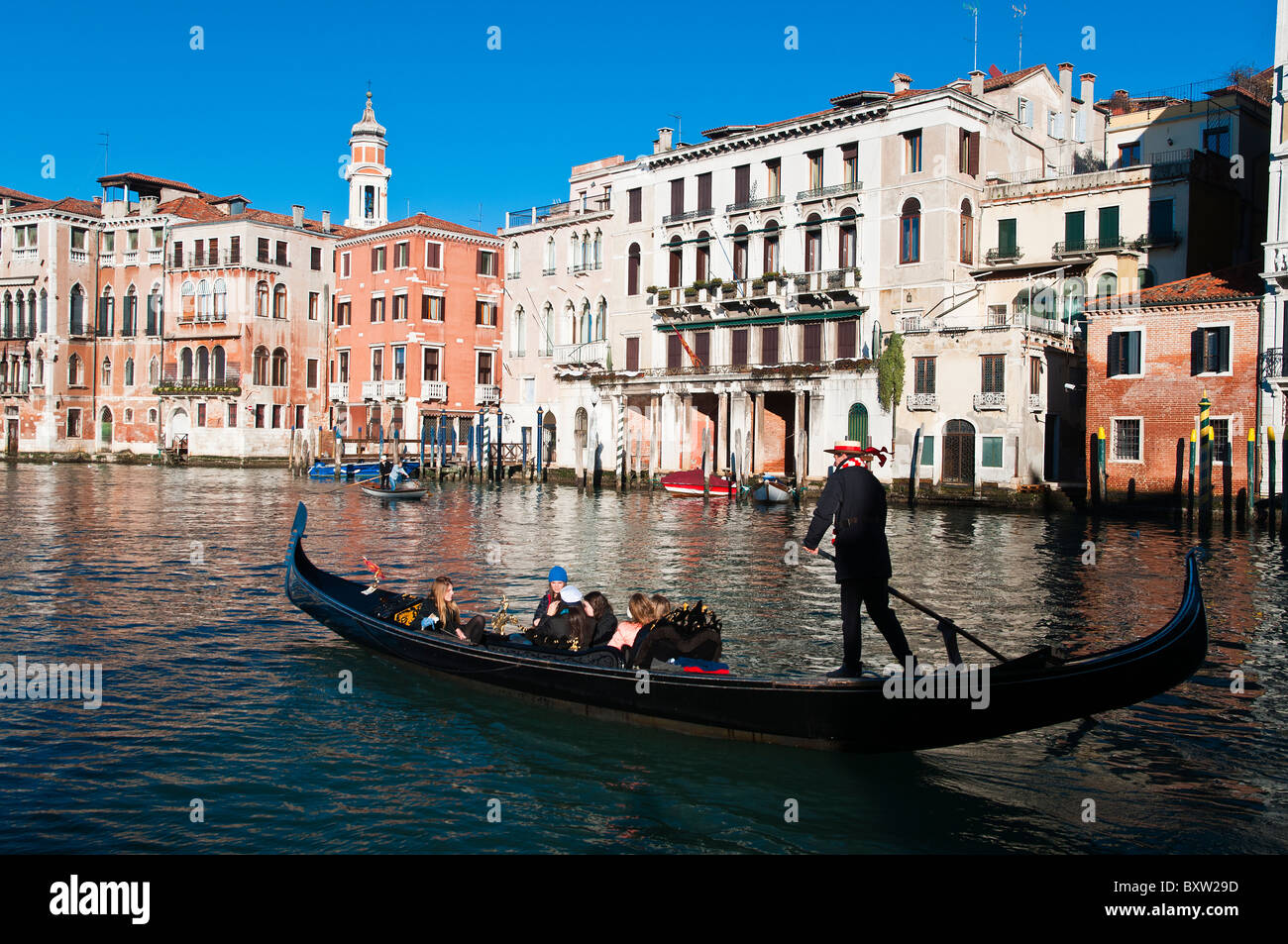 Gondola and gondolier with tourists on Grand Canal (Canal Grande), Venice, Italy - Stock Image