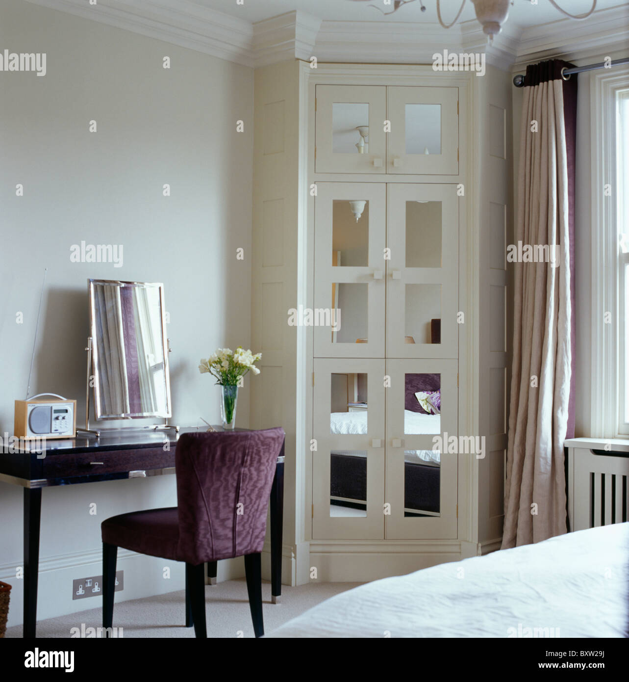 Mirrored Glass Panels In Fitted Corner Wardrobe In Bedroom With Purple  Velvet Chair At Simple Dressing Table