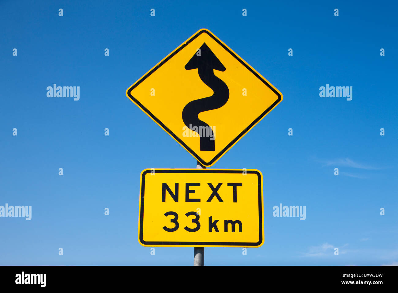 Australia, Victoria, Port Campbell, Winding Road Next 33km warning sign along Great Ocean Road - Stock Image
