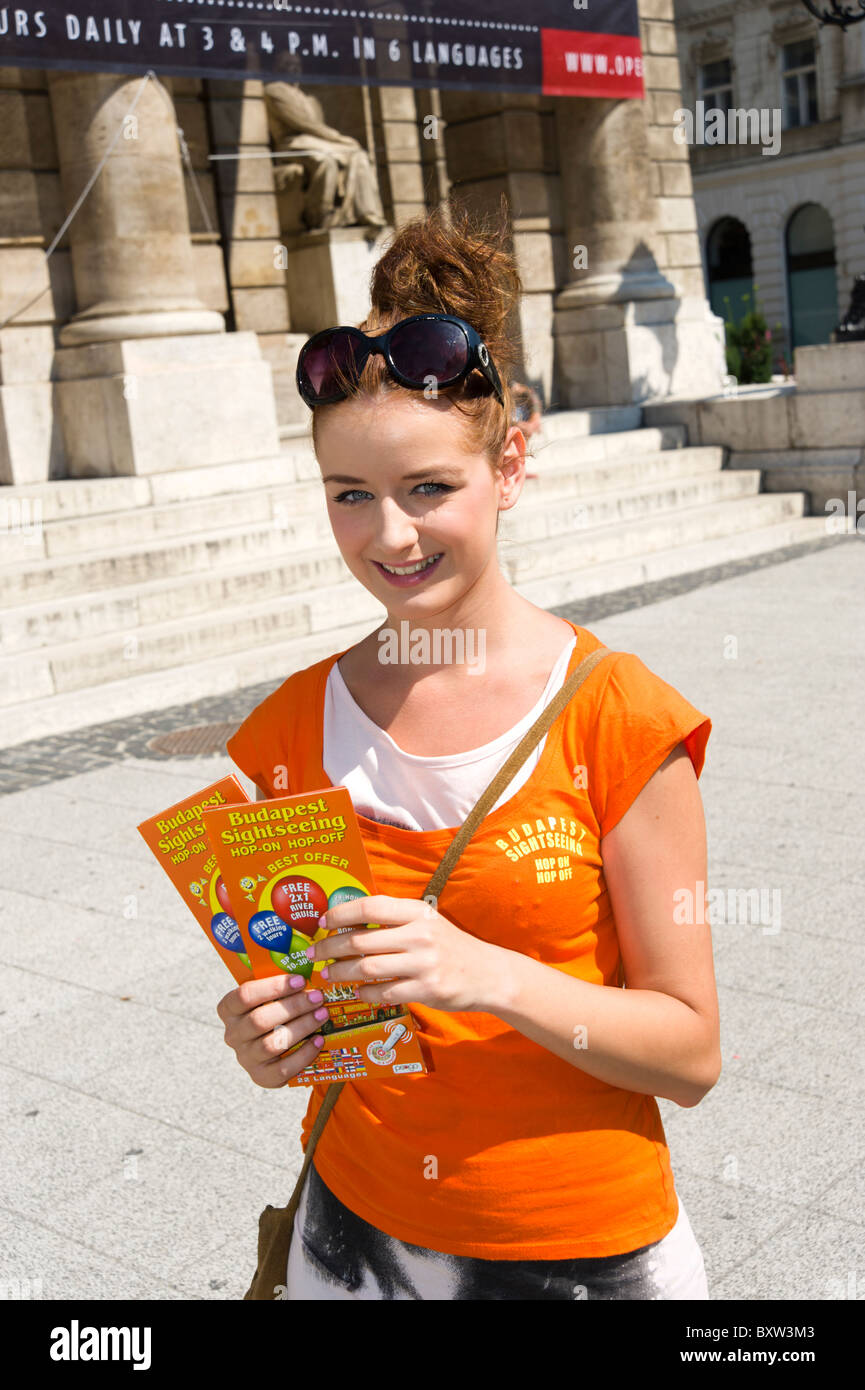 Teenager handing out leaflets for the hop on hop off city sightseeing bus tour, Budapest, Hungary - Stock Image