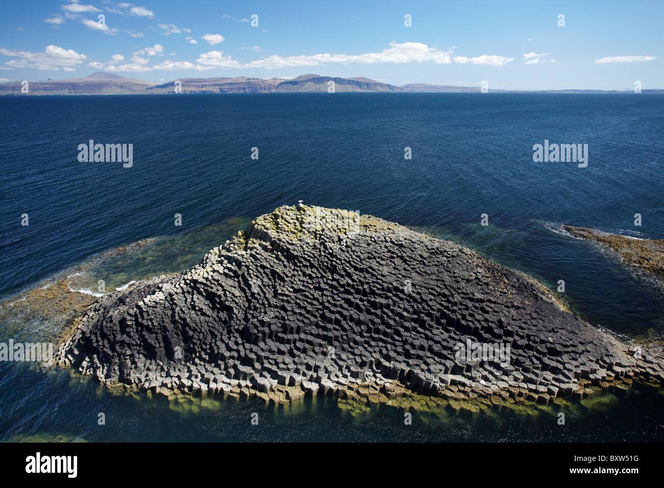 Polygonal basalt, Am Buachaille rocks, Staffa, off Isle of Mull (in distance), Scotland, United Kingdom Stock Photo