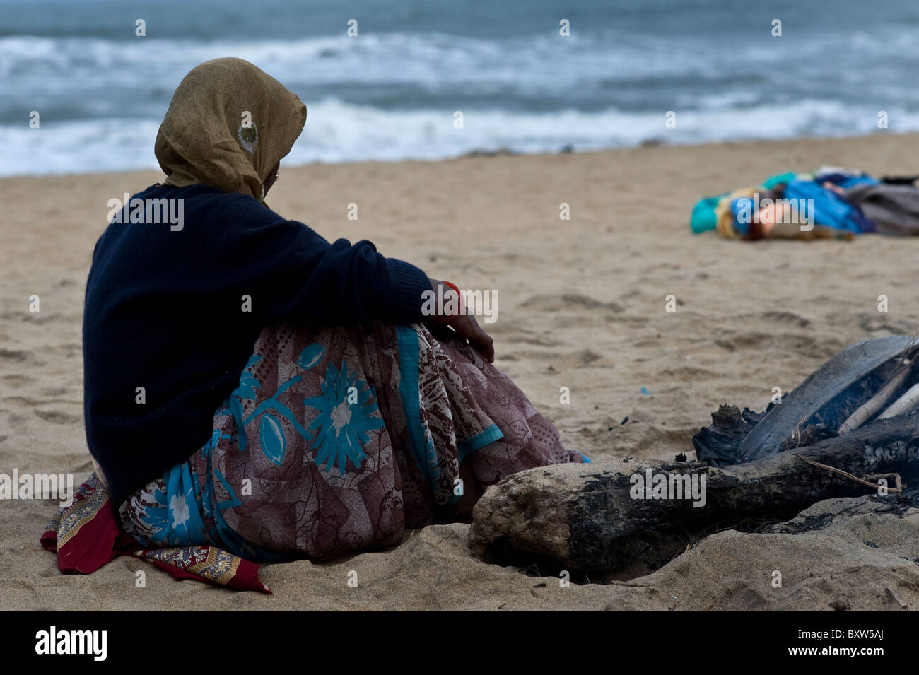Beach seller staying warm on a cool day in South India near Mamallapuram - Stock Image