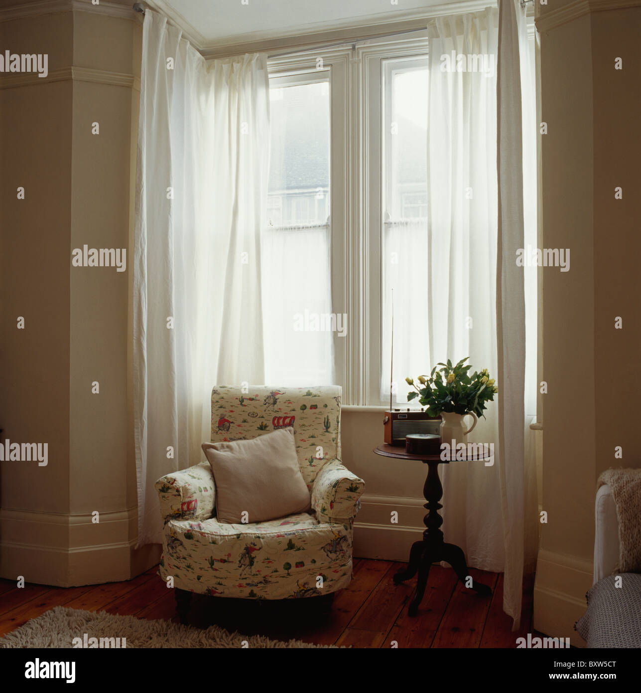 Patterned Cream Armchair In Front Of Bay Window With White Voile Curtains
