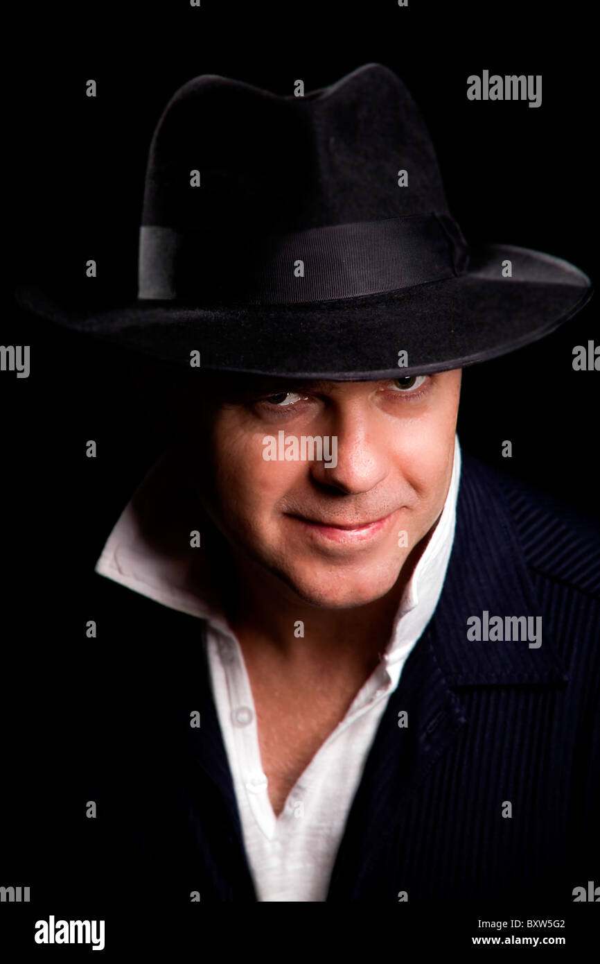 A mature male artist singer wearing a black Fedora hat and blue suede  jacket posed looking ff6e4748e02
