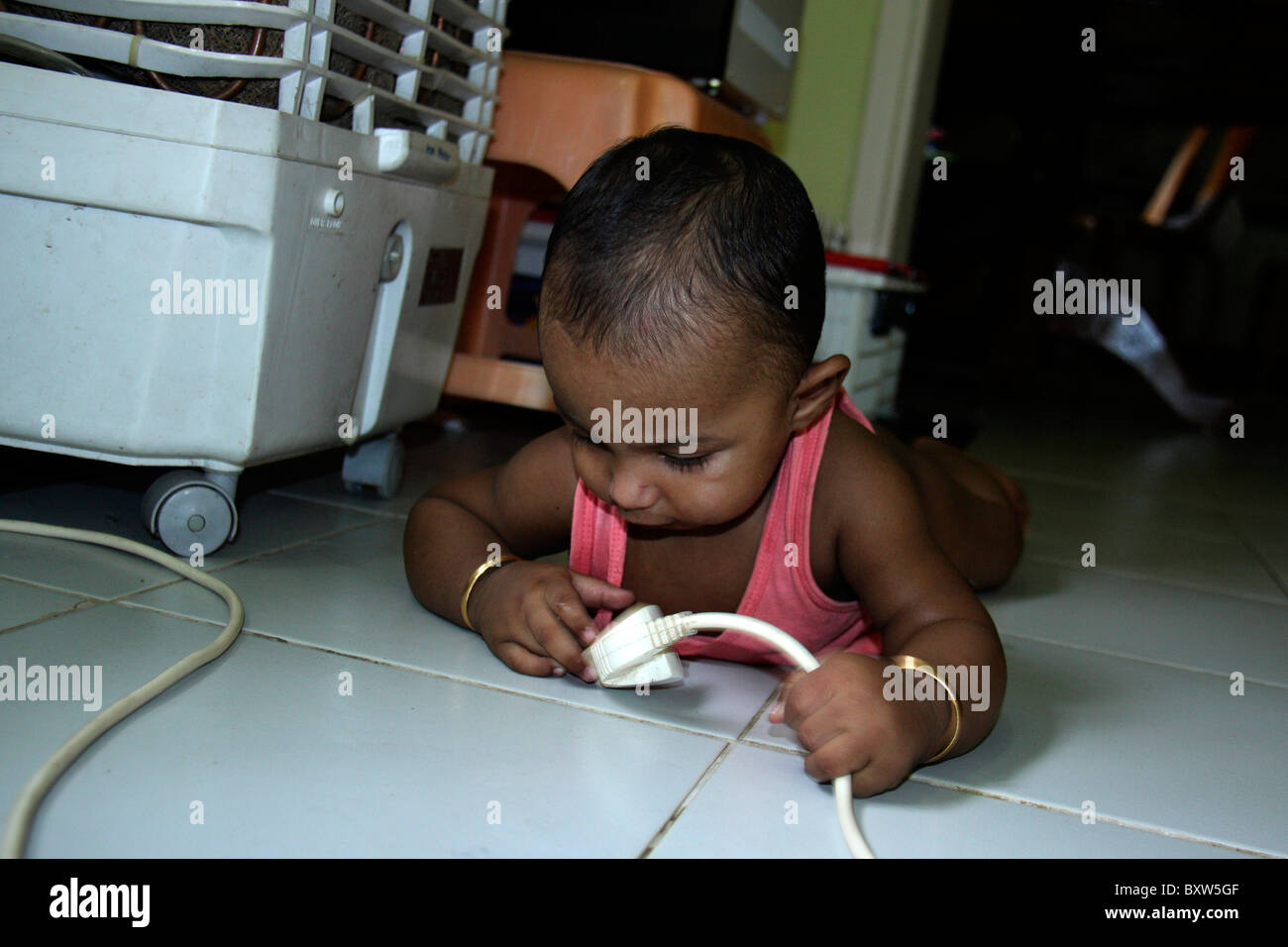 small child playing dangerously  with electrical cable carelessly,an example of parents negligence of childcare. - Stock Image