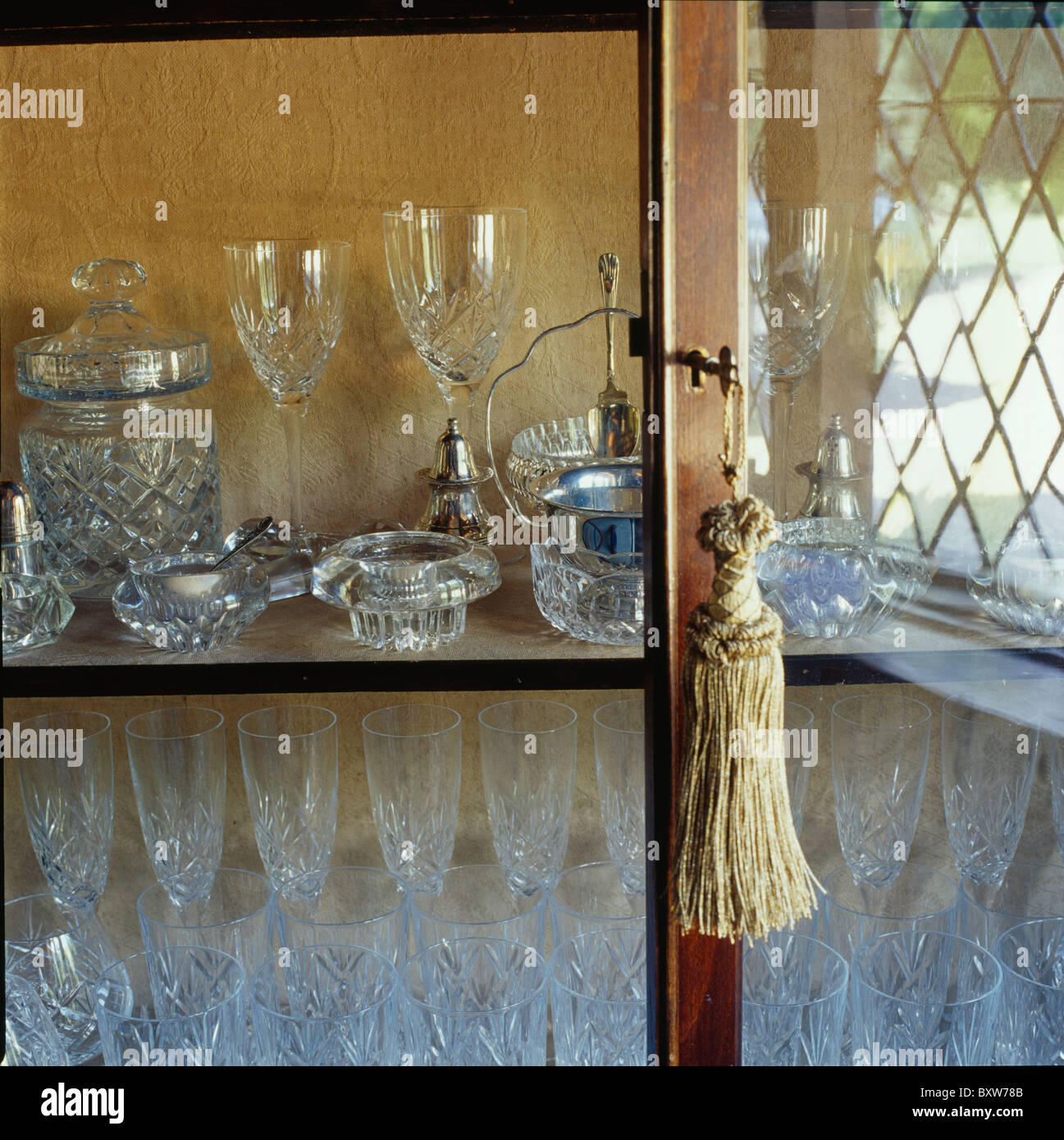 Close Up Of Tassel On Glass Door Antique Cupboard With Display Wine Glasses And Salt Pots