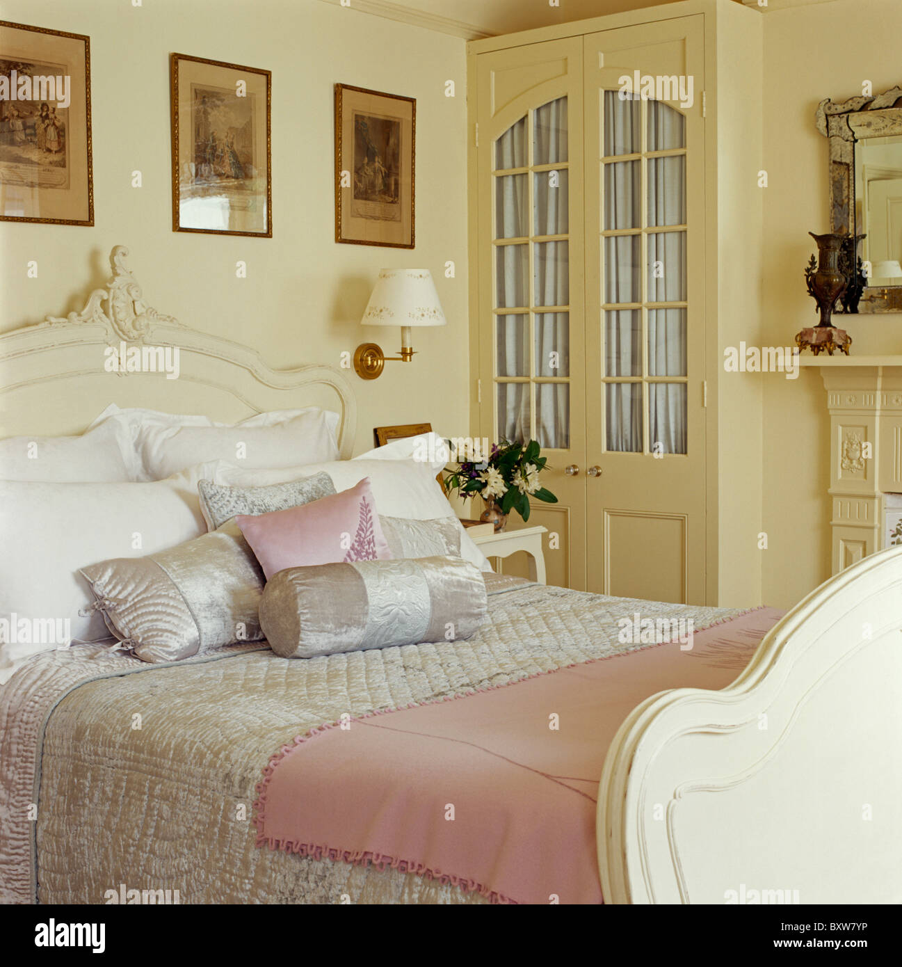 Pale gray silk quilt and cushions on cream bed with pink ...
