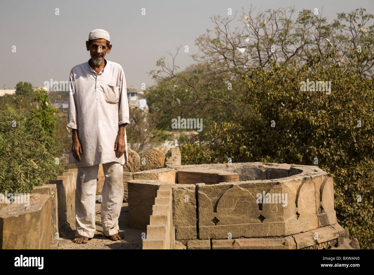 A Muslim man stands on the roof of the Bai Harir Mosque at Ahmedabad, Gujarat, India. - Stock Image