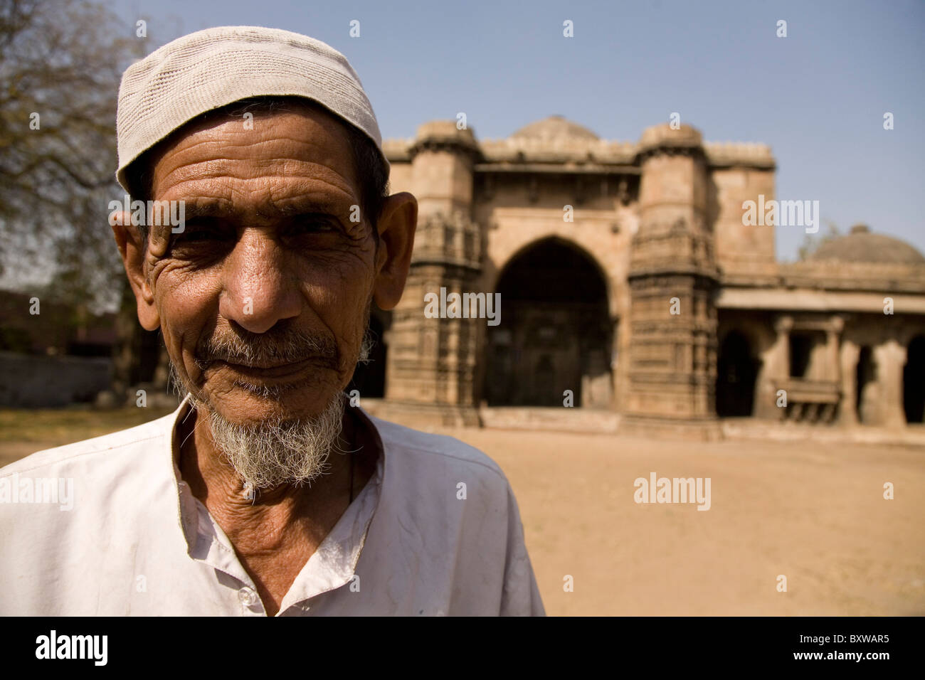 A Muslim man in a prayer cap stands in front of the Bai Harir Mosque at Ahmedabad, Gujarat, India. - Stock Image