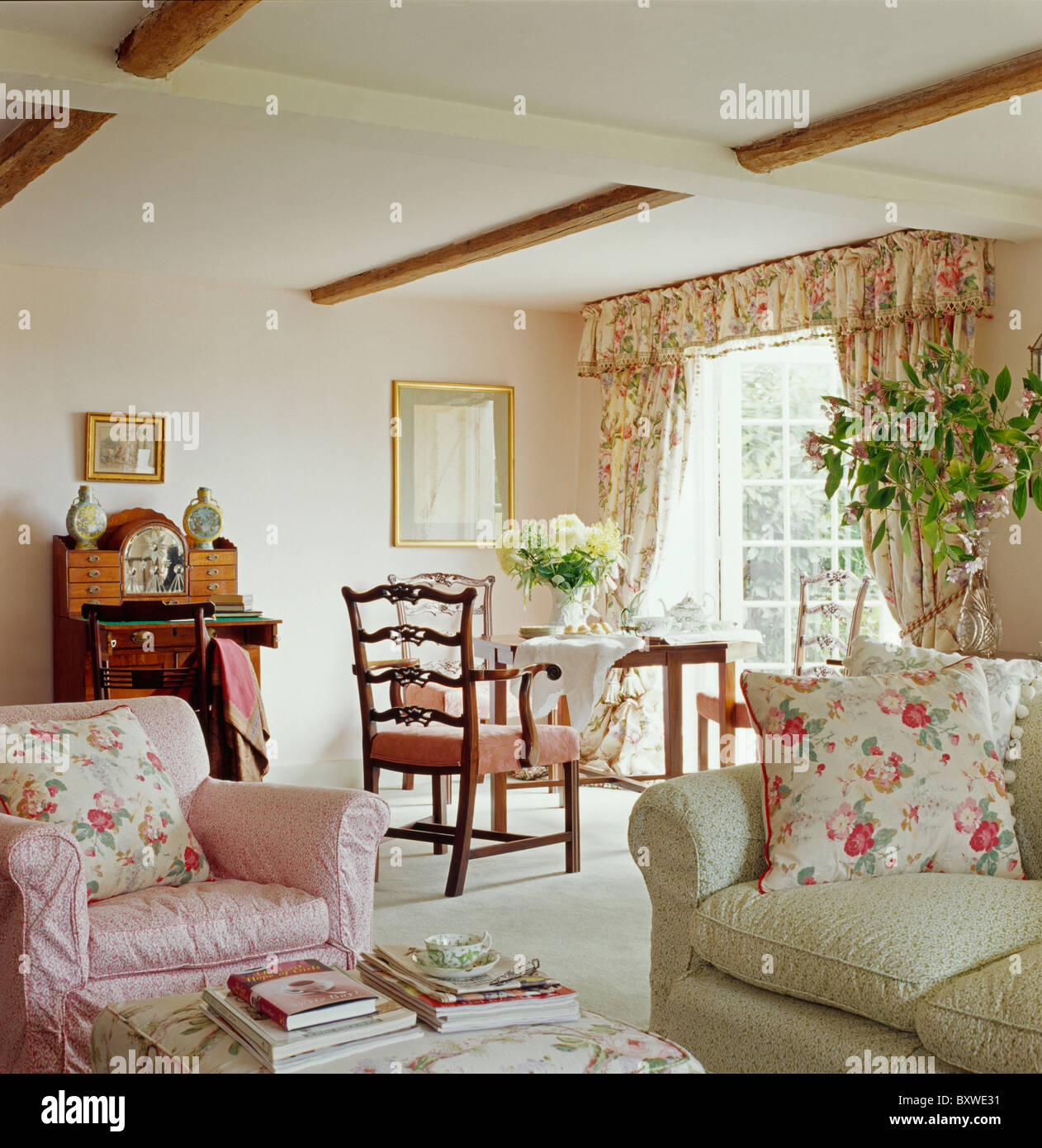 Pink Floral Cushions On Pink Armchair And Pale Green Sofa