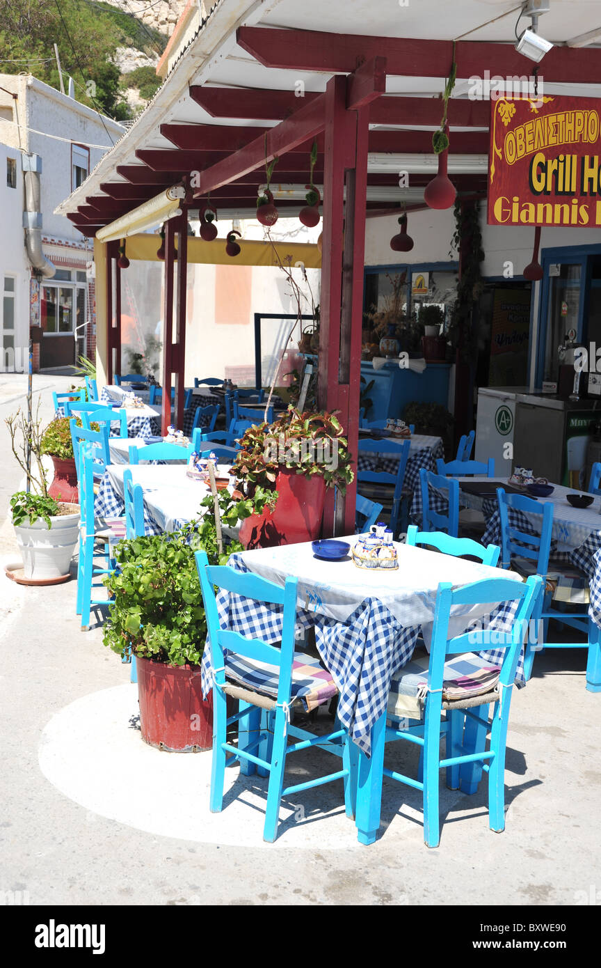 Traditional Greek restaurant with blue tables and chairs in Matala, Crete, Greece - Stock Image