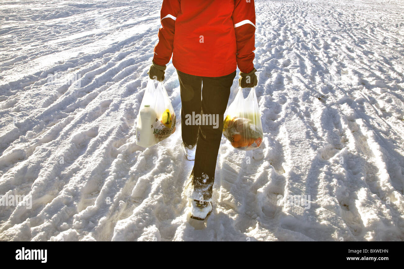 Person trudging through the snow with two shopping bags. - Stock Image
