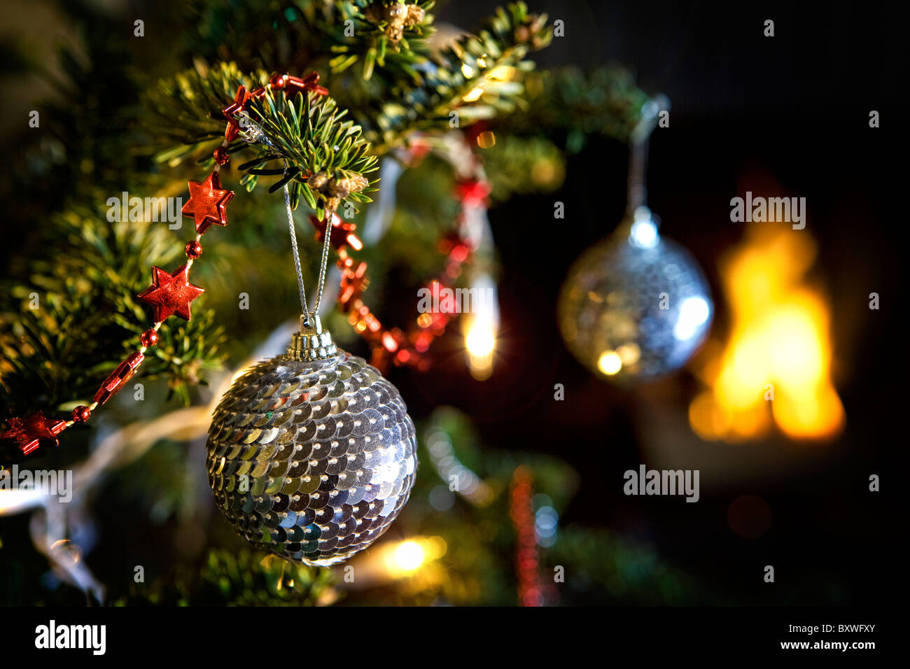 Disco mirror ball decorations hanging from a Christmas tree in front of a fire on Christmas eve - Stock Image