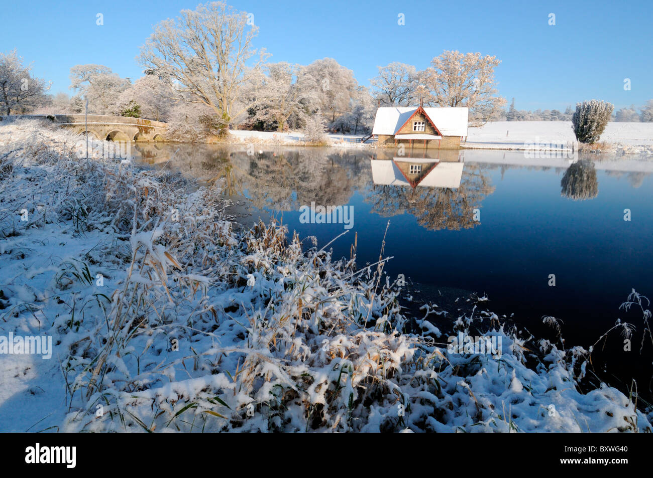 boathouse lake reflect reflection carton hall estate maynooth ireland winter wonderland snow ice frost blue sky - Stock Image