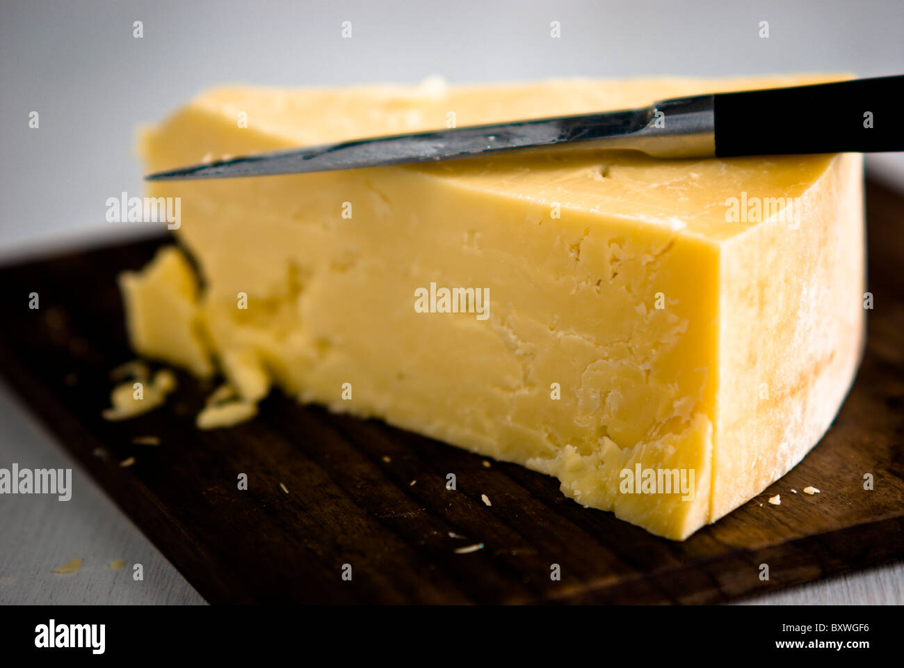 Wedge of cheddar cheese, being cut on wooden cheeseboard - Stock Image