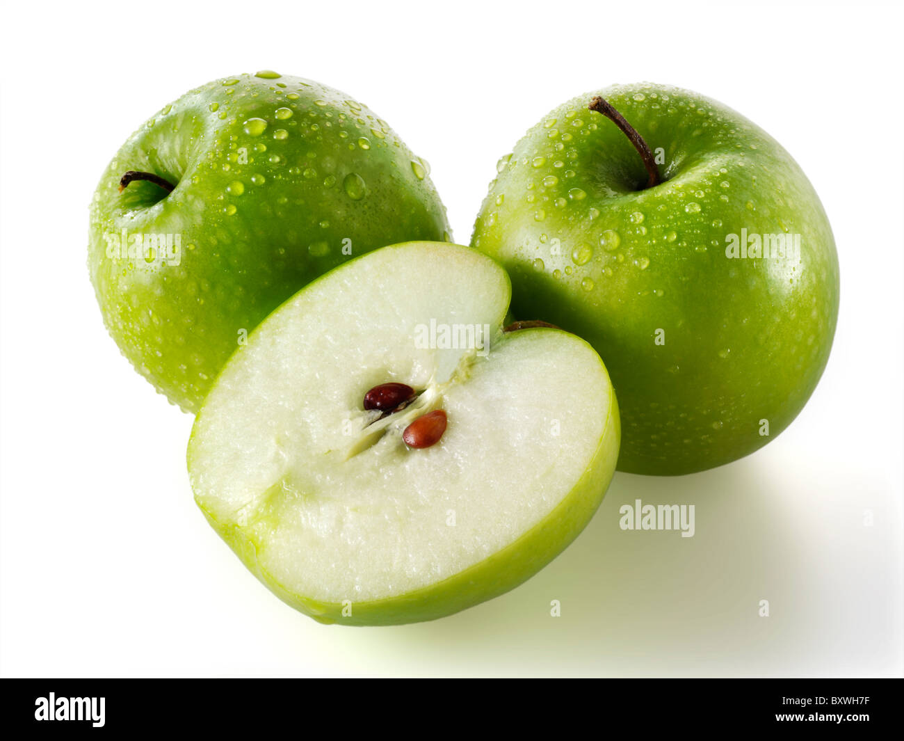 Whole & cut Granny Smiths apples - Stock Image
