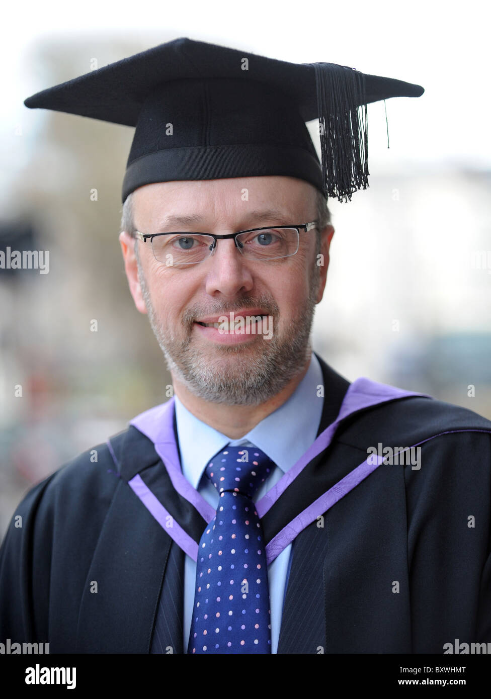 Happy smiling mature male student graduate about to pick up his degree from Sussex University - Stock Image