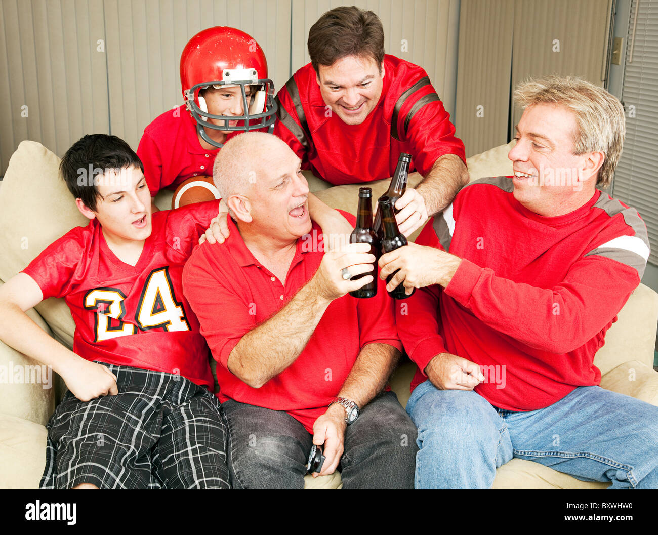 Superbowl football fans toasting success with their beer bottles.  - Stock Image