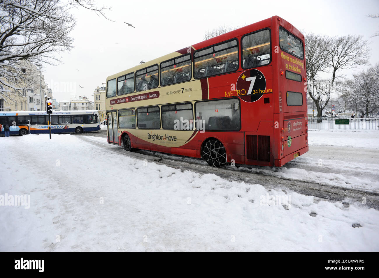 A bus using snow chains drives through Brighton after heavy snowfall covers the roads - Stock Image