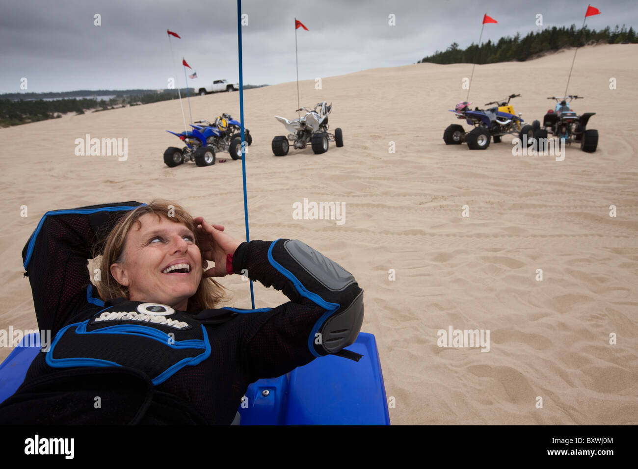 USA, Oregon, North Bend, Becky Selba rests while riding her ATV on sand dunes at Oregon Dunes National Recreation - Stock Image