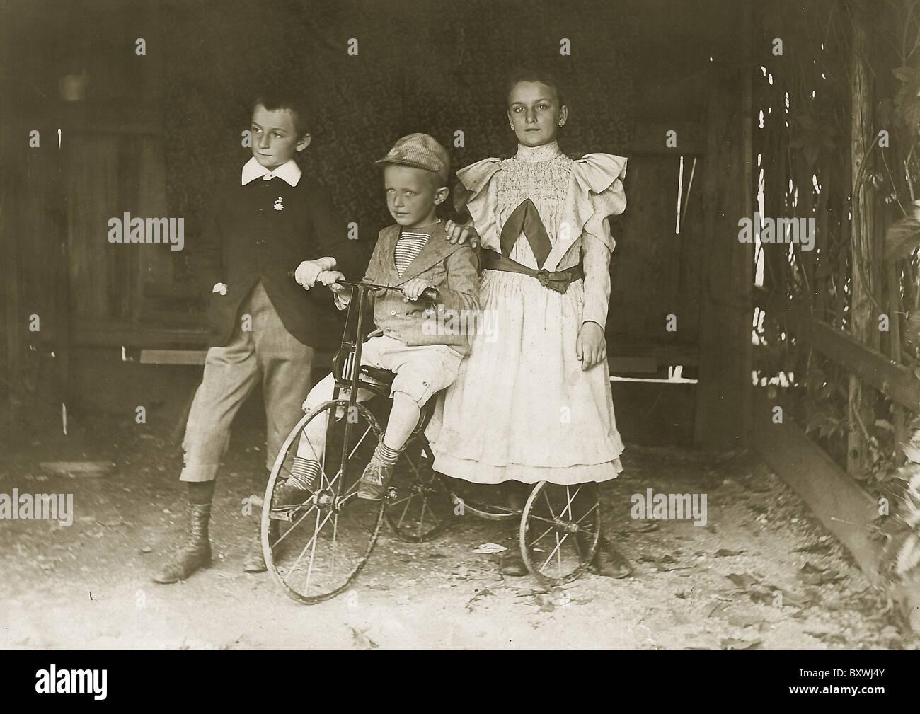 Three siblings share a bike. circa: 1900-1910 Stock Photo