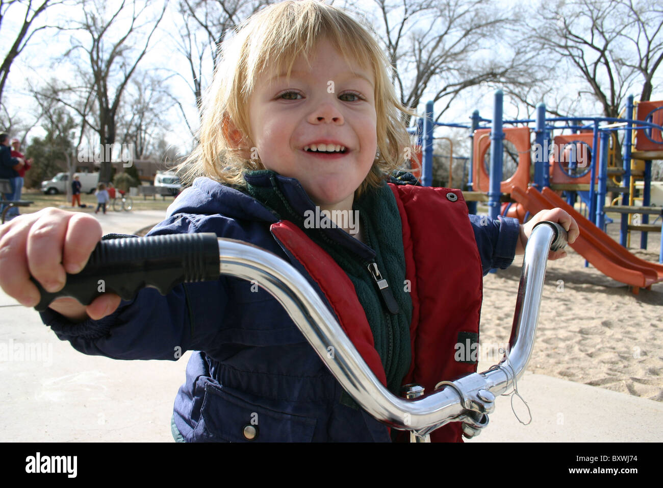 Two year old boy proudly riding a bicycle, holding large handle bars at a park. - Stock Image