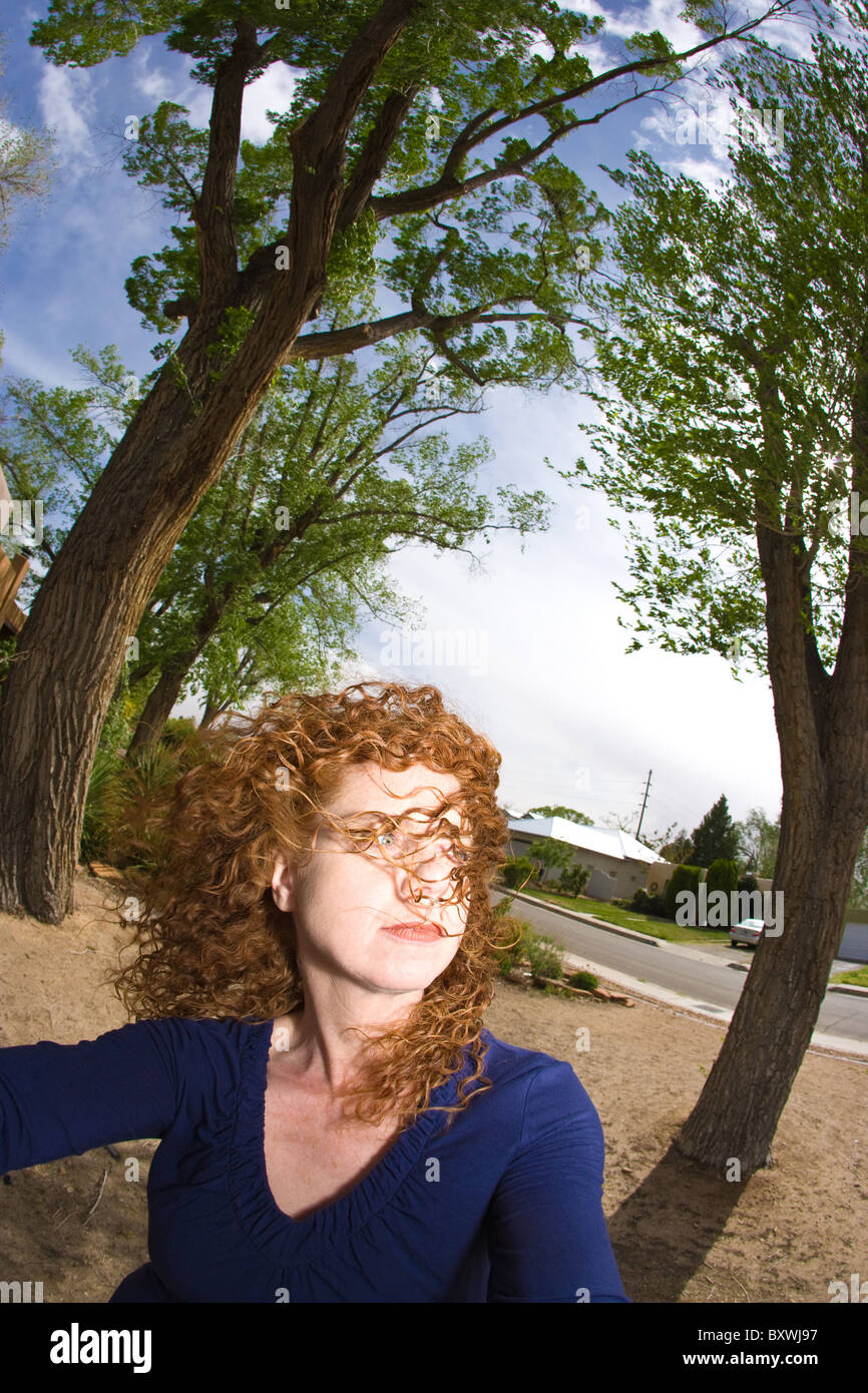 Woman with red curly hair blowing in the wind, trees in background, fish eye lens. - Stock Image