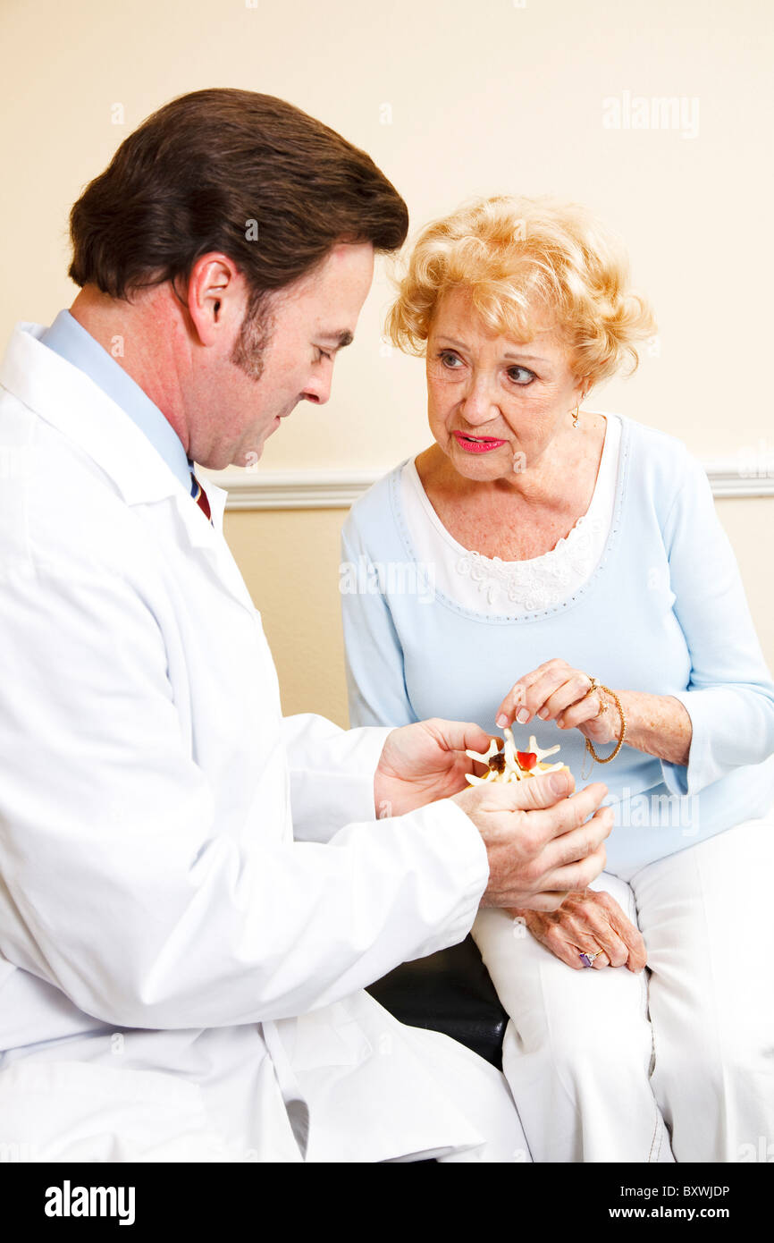 Chiropractor shows senior patient a model of the spine and discusses her treatment plan. - Stock Image