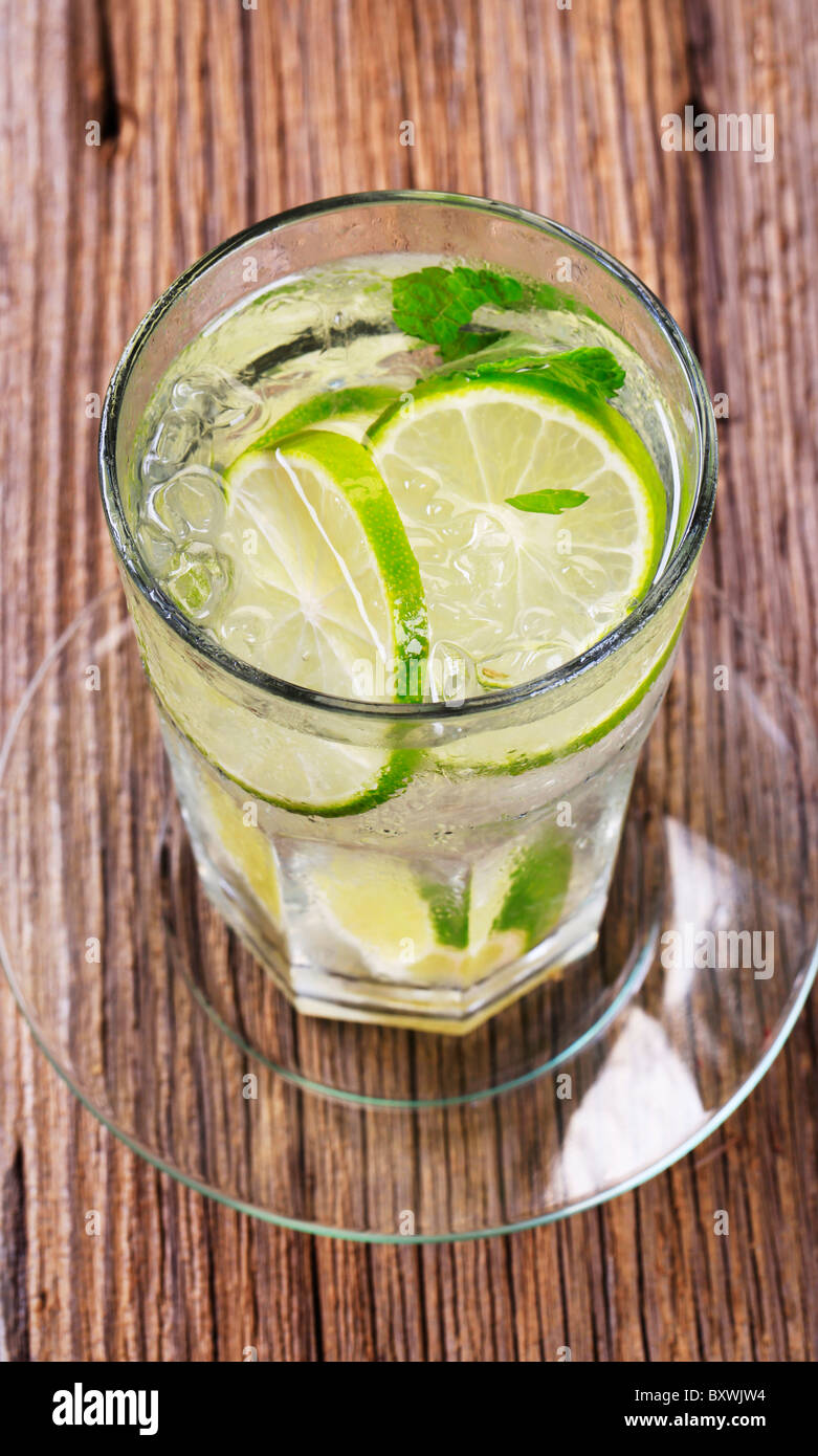 Glass of cold drink with slices of lime - Stock Image