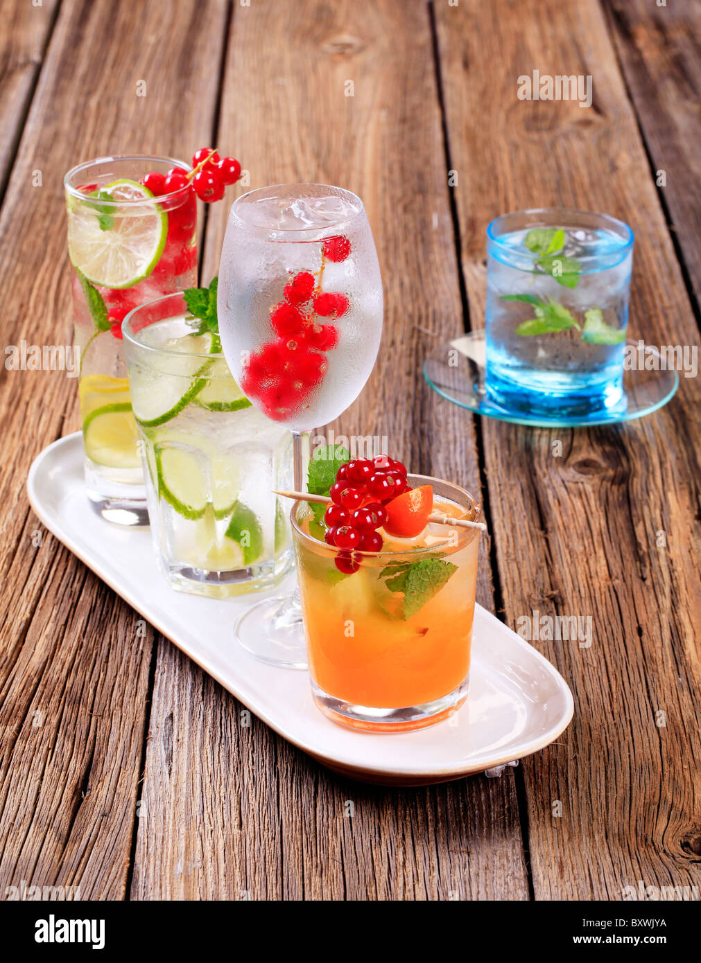 Glasses of iced drinks garnished with fresh fruit - Stock Image