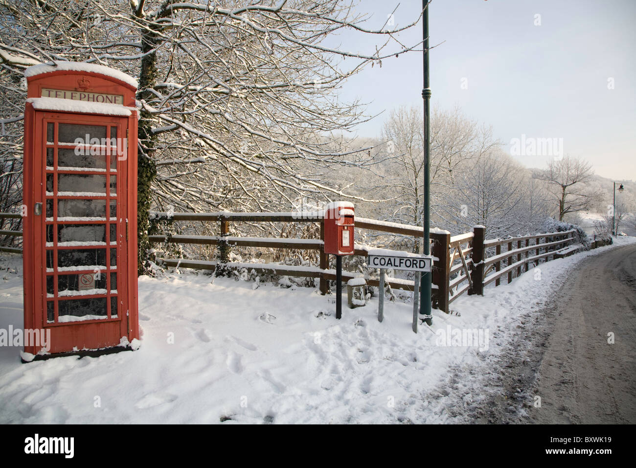 Telephone Box and Post Box by the side of a road during winter snow. - Stock Image