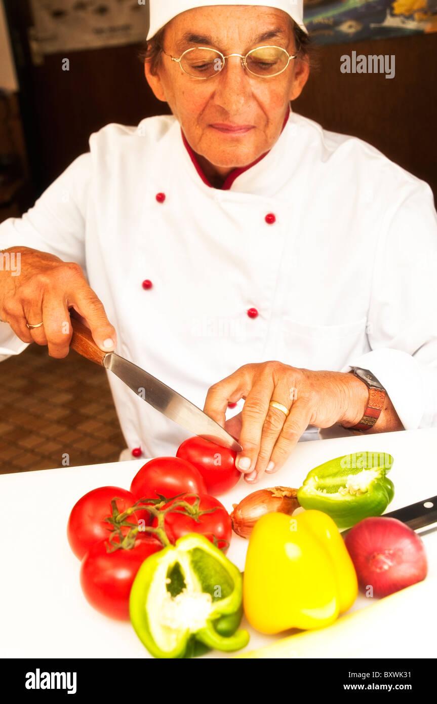 A woman is preparing a meal, cutting vegetables, eine frau bereitet einen Salat vor und schneidet Gemüse - Stock Image