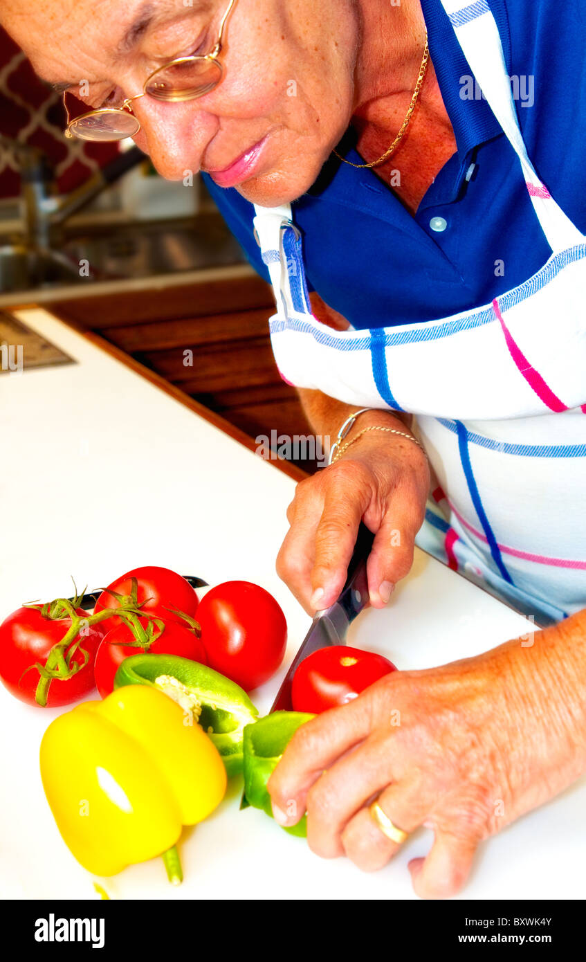 A woman is preparing a meal, cutting vegetables; eine frau bereitet einen Salat vor und schneidet Gemüse - Stock Image