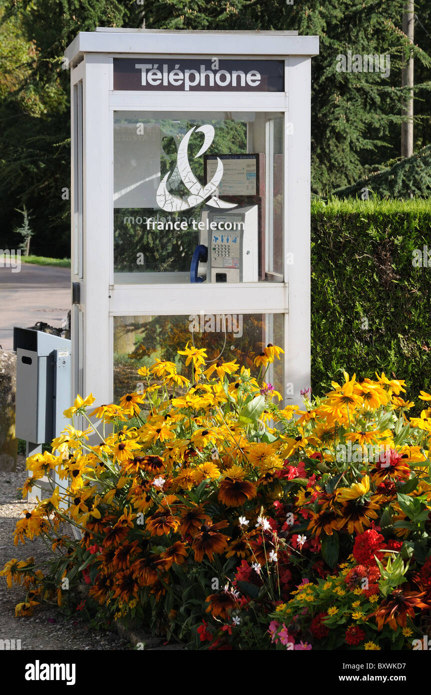 Telephone kiosk cabin box for France Telecom in Chablis town Burgundy France with flowers in street garden - Stock Image