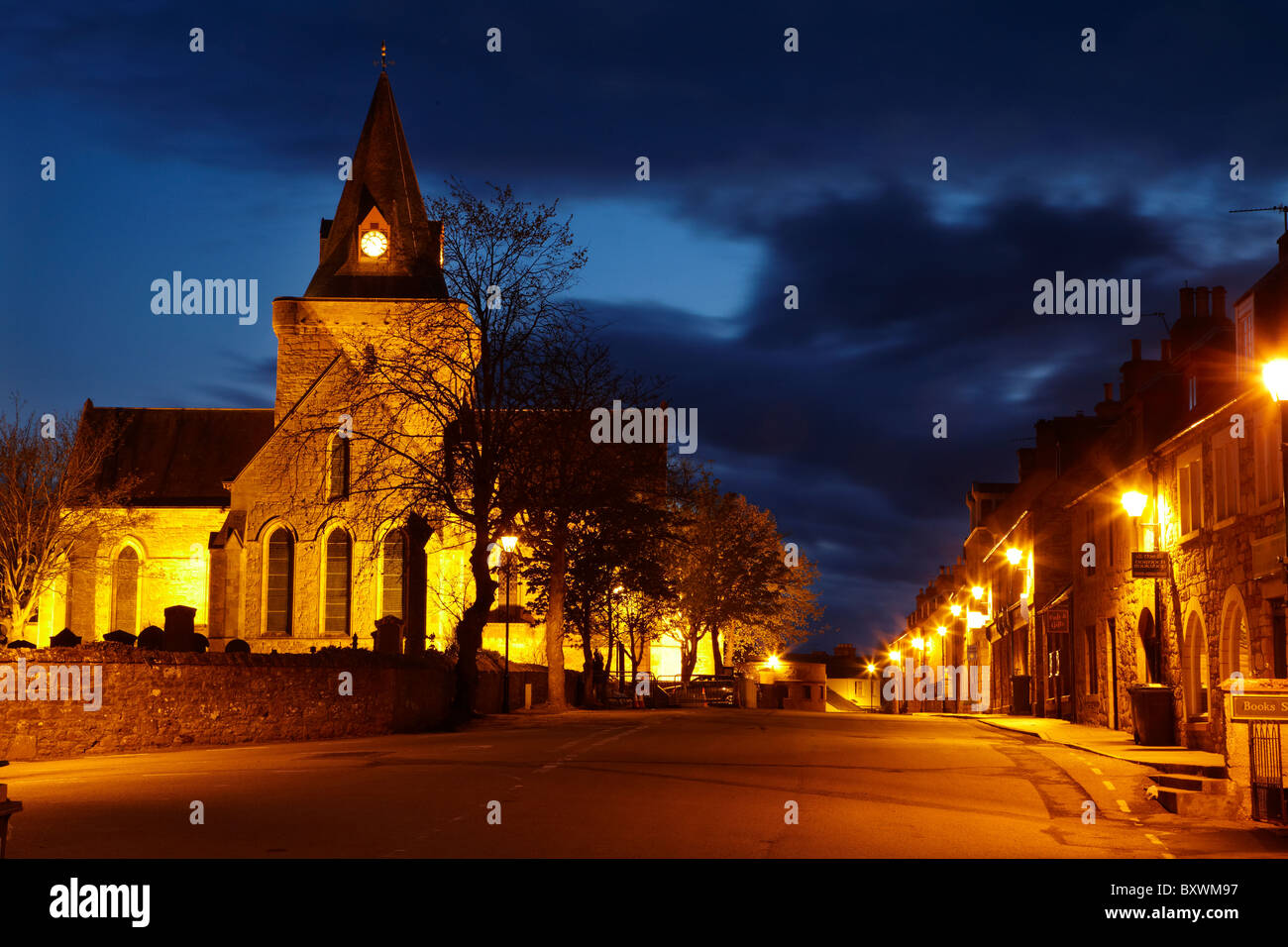 Dornoch Cathedral, floodlit at night (built in the 13th century), and Hight Street, Dornoch, Highlands, Scotland, - Stock Image