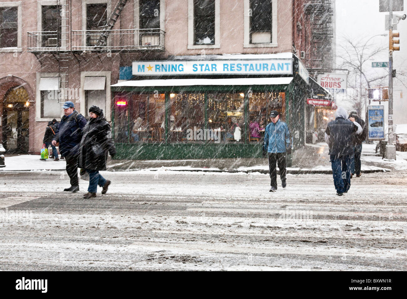 warmly dressed pedestrians cross 57th Street as driving blowing snow falls during December 2010 blizzard New York - Stock Image