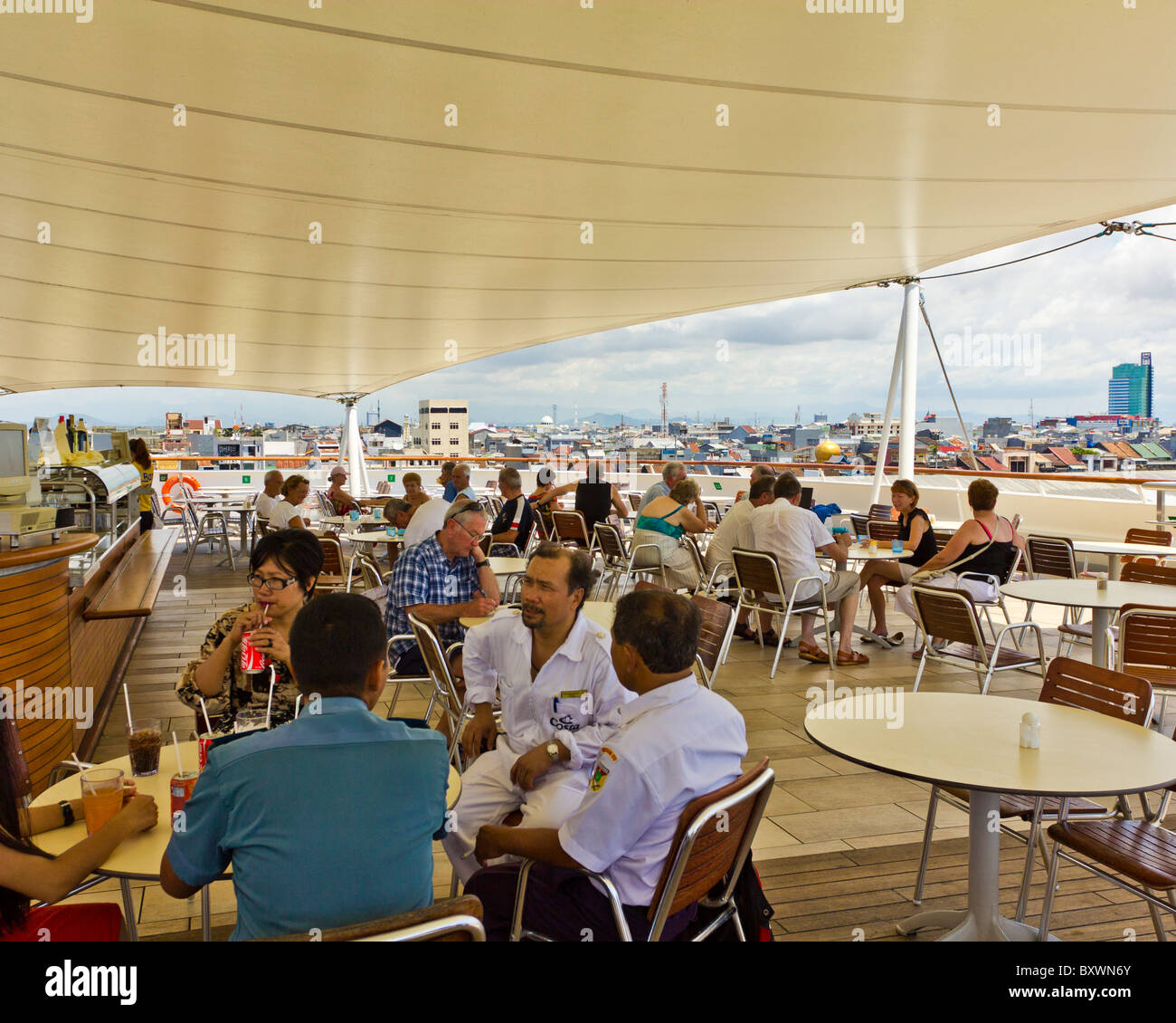 Passengers relaxing at the rear deck bar of Costa Romantica cruise ship with Indonesian City of Makassar in the - Stock Image