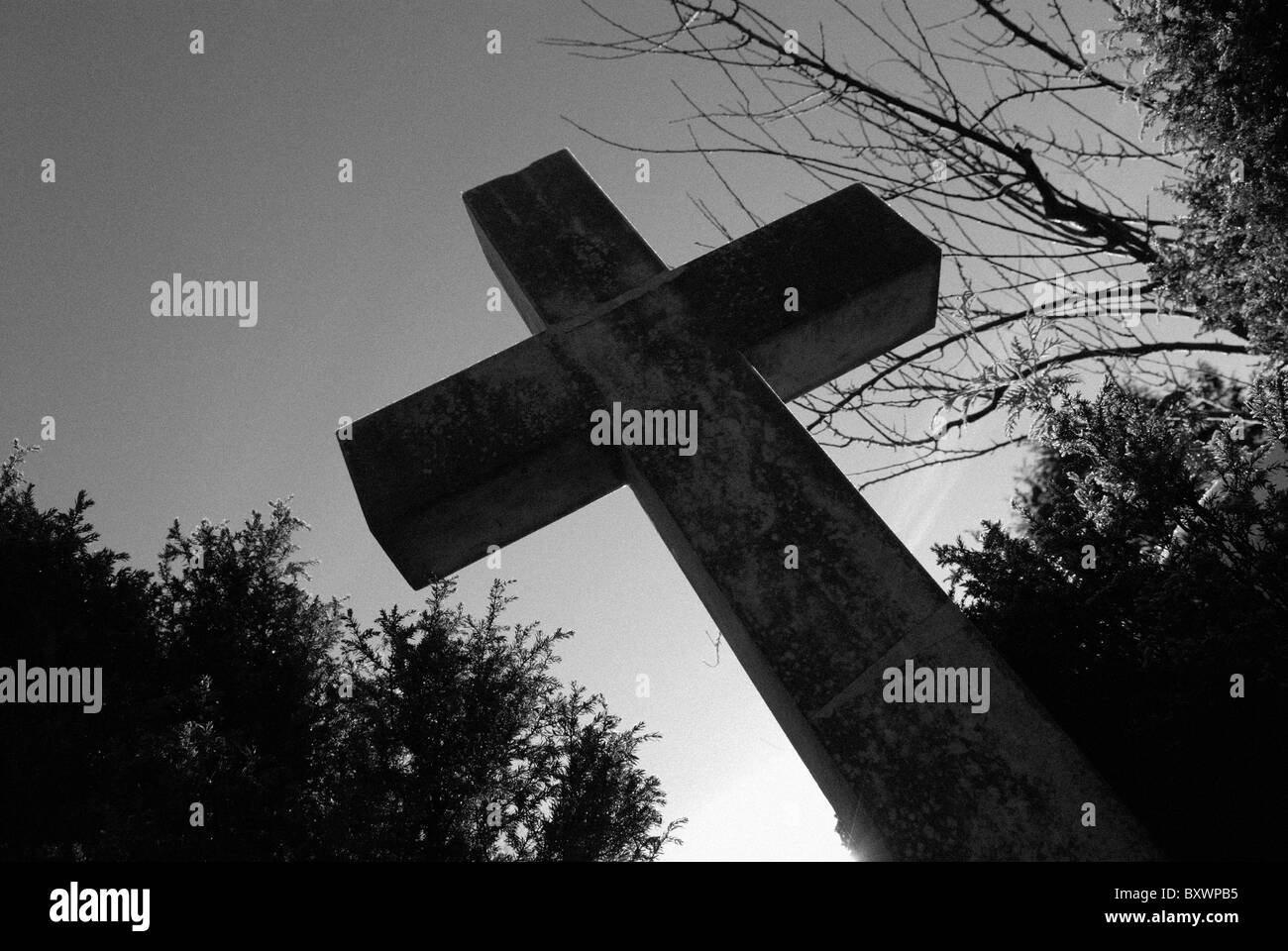 STONE CROSS SILHOUETTED - Stock Image