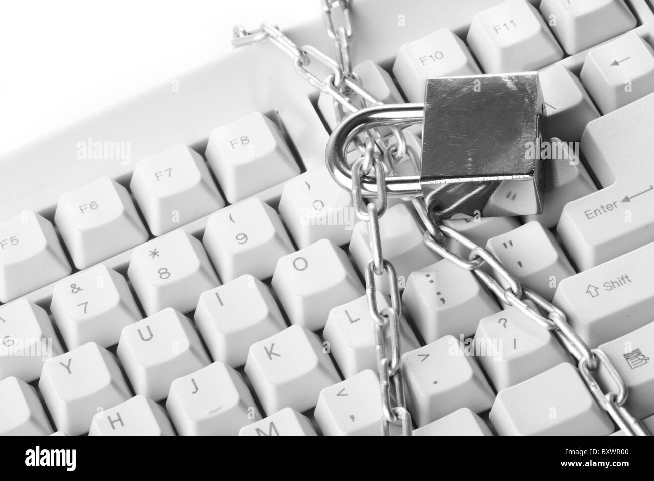 Computer keyboard secured with chain and padlock - Stock Image