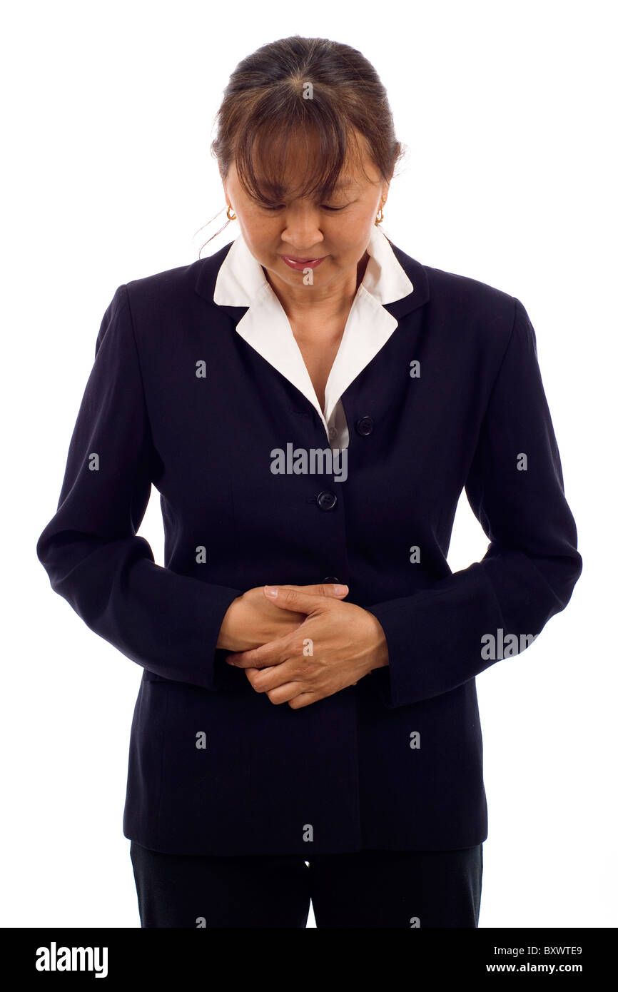 Mature Asian woman with stomach issues isolated over white background - Stock Image