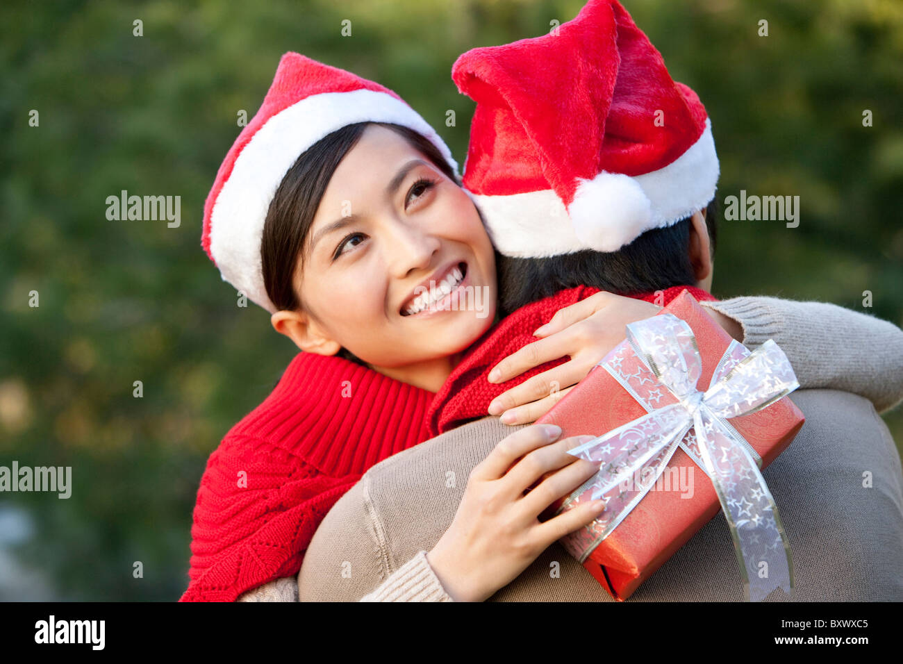 Young Woman Embraces Young Man while Holding Christmas Gift - Stock Image