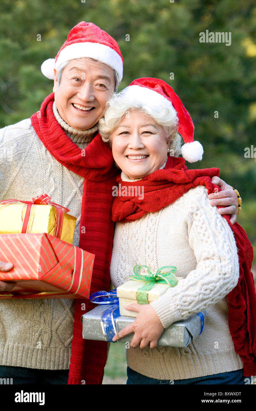 Senior Couple in Santa Hats Holding Christmas Gifts Stock Photo