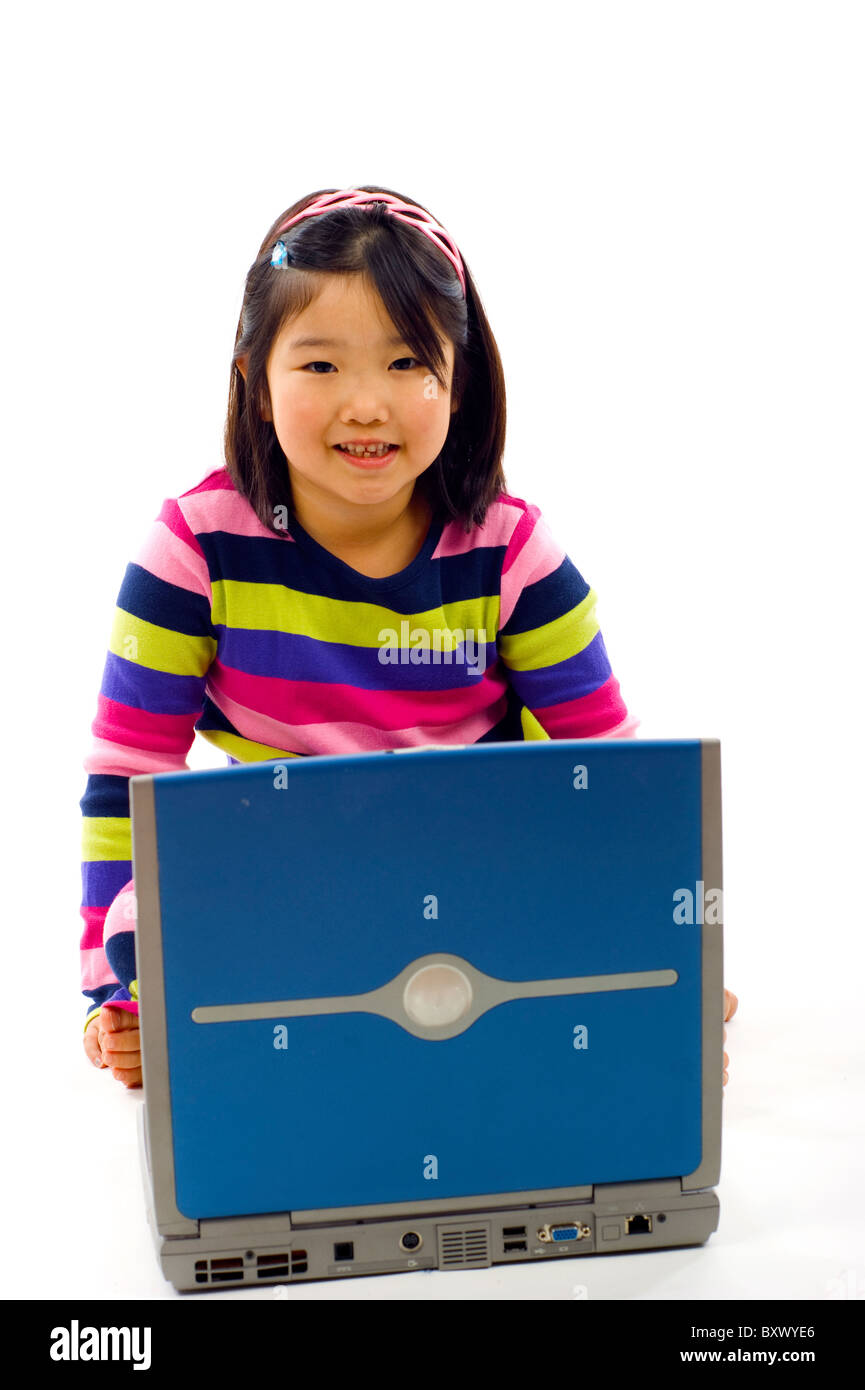 Adorable little Asian girl working on laptop , isolated over white - Stock Image