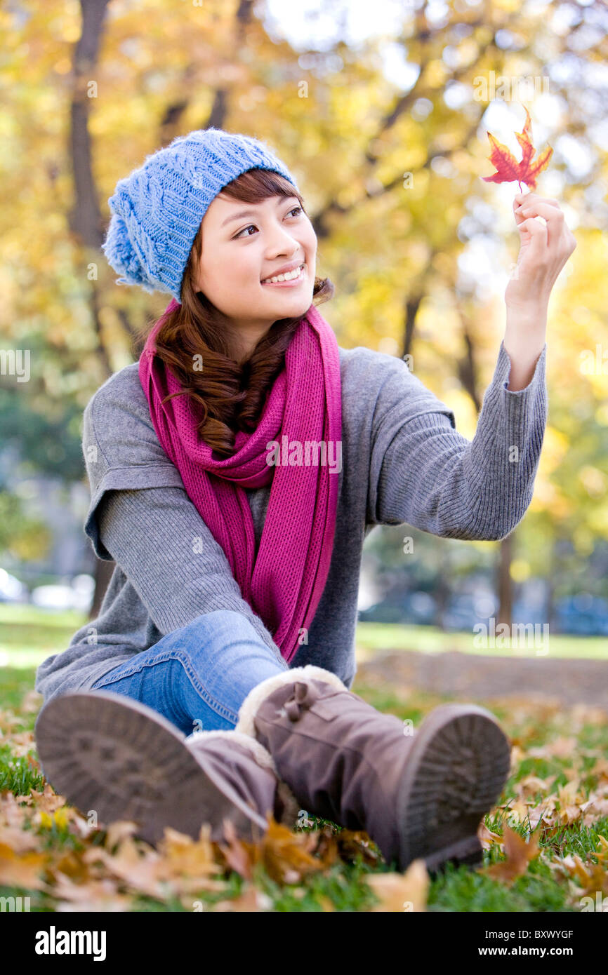 Young Woman Looking At Maple Leaf Stock Photo