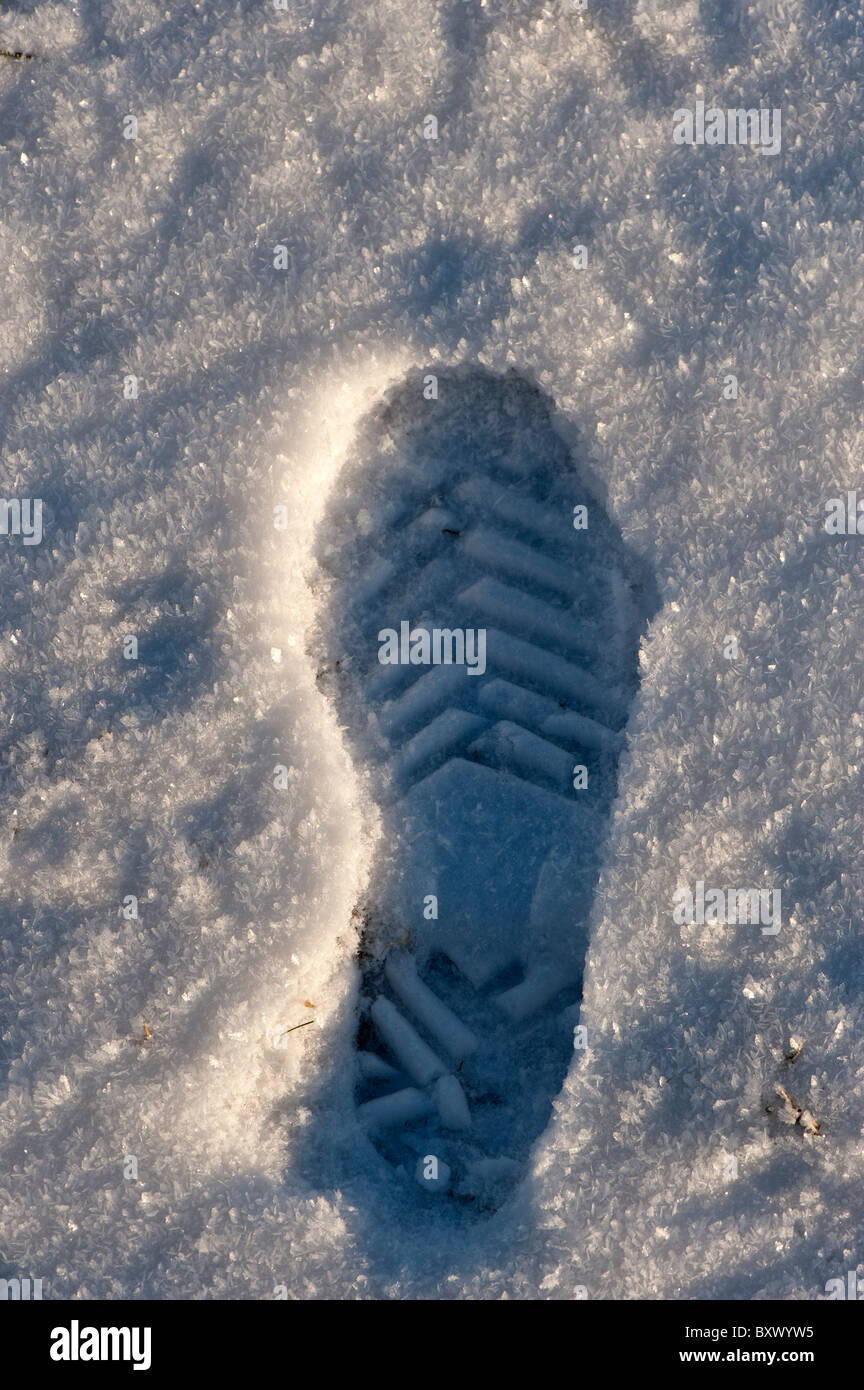 Shoe footprint in snow, showing strong tread for good grip. - Stock Image