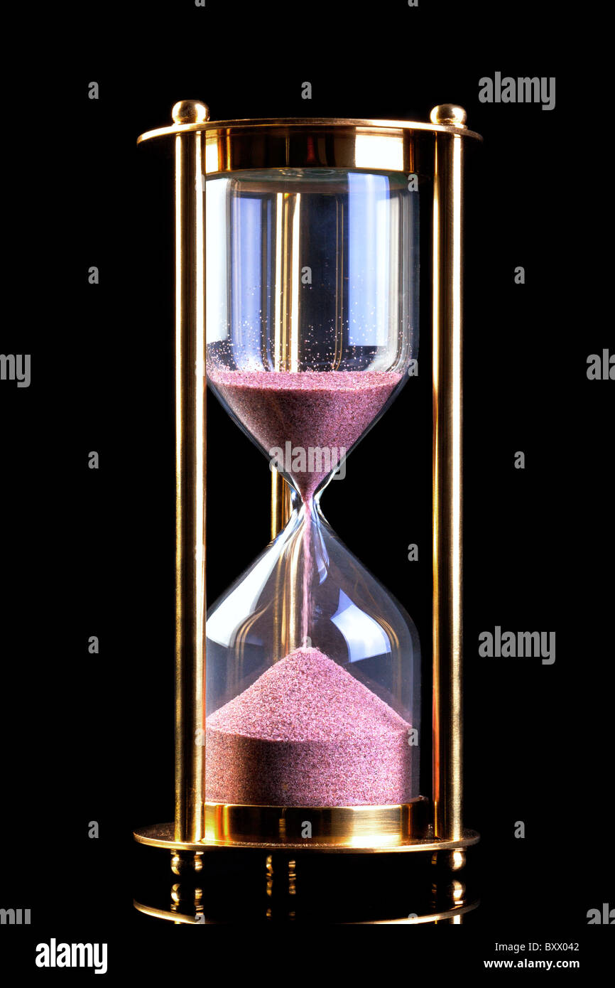A brass hourglass or sand timer isolated on a black background. - Stock Image