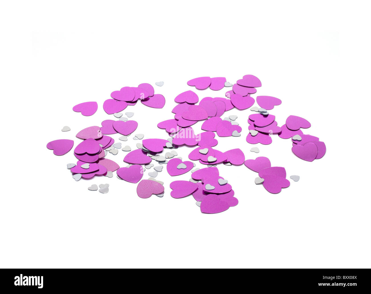 Pink and silver heart shaped confetti on white background - Stock Image
